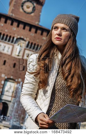 Rediscovering things everybody love in Milan. modern traveller woman near Sforza Castle in Milan Italy with map