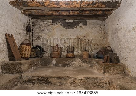 Basement of an old house with wooden beams and wall with humidity, antique household items, carboy demijohn, stewpot, plank, Wicker basket, pulley with chain, yuguillo