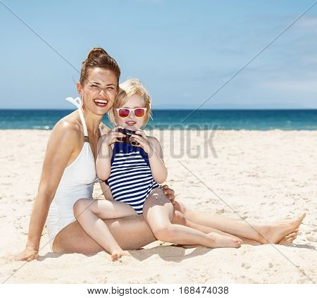 Happy Mother And Child At Beach Looking On Photos In Camera