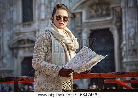 Modern Woman In Milan, Italy With Map Looking Into Distance