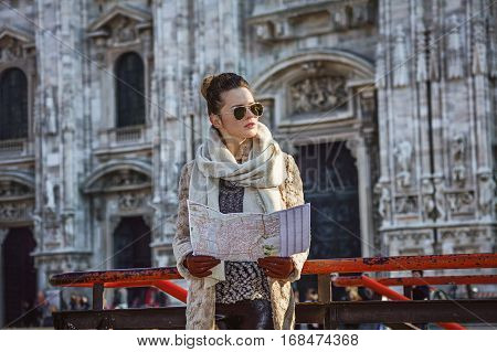 Rediscovering things everybody love in Milan. elegant woman in fur coat and sunglasses in the front of Duomo in Milan Italy with map looking into the distance