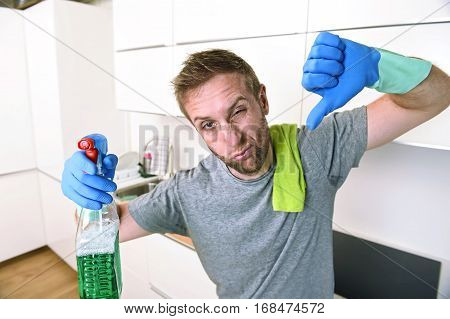 young sad man in rubber gloves cleaning with detergent spray washing and making home kitchen sink clean feeling tired and bored in home work and single man domestic wash labor concept