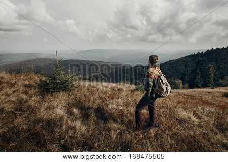 hipster traveler with backpack posing on top of mountains. wanderlust and travel concept with space for text. stylish man hiking. atmospheric epic moment