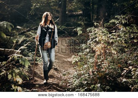 Happy Hipster Traveling And Smiling, Walking In Woods In Light. Wanderlust And Travel Concept With S
