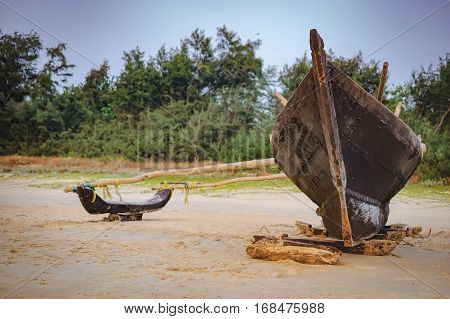 Traditional fishing boat on palm trees background Cavelossim Beach in South Goa, India