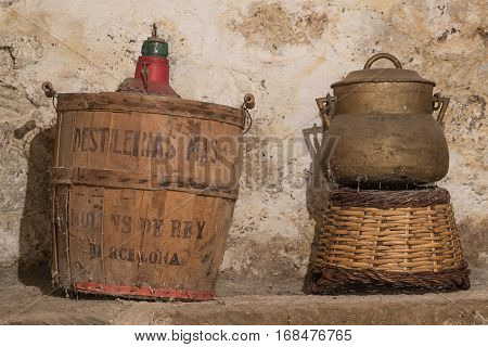 Antique carboy spanish demijohn and stewpot abandoned at the storage of an old house, with cobwebs and wall with humidity