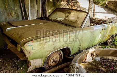 A battered abandoned old green car in Guatemala