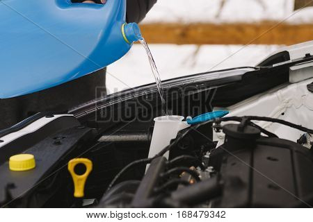 Car maintenance. Man pouring car winter windshield washer fluid outdoor. Closeup image taken outdoors.