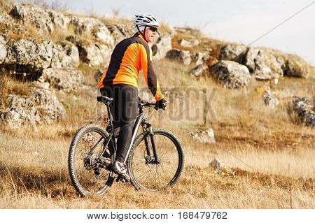 Mountain Bike cyclist riding single track in valley in countryside. spring season. sunny day. beautiful landscape. cyclist in the helmet.