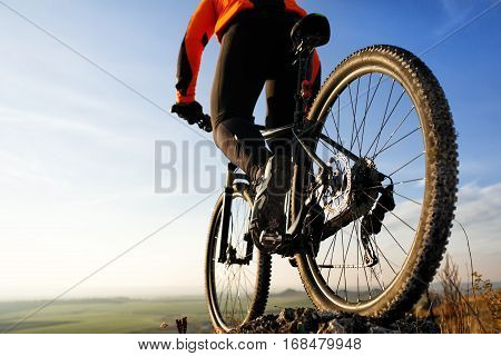 back view of a man with a bicycle against the blue sky. cyclist rides a bicycle. Rear view people collection. backside view of person. blue sky background and mound.