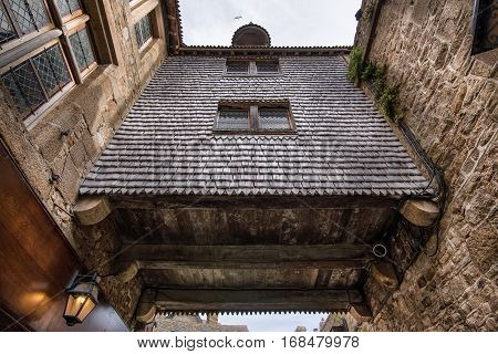Huge wooden balcony between two stone houses in Mont Saint-Michel, Normandy, France
