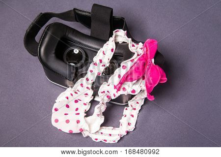 Virtual reality glasses for mobile devices with dotted pink white lingerie with bow on top, vr technology used for porn vr video in adult entertainment.