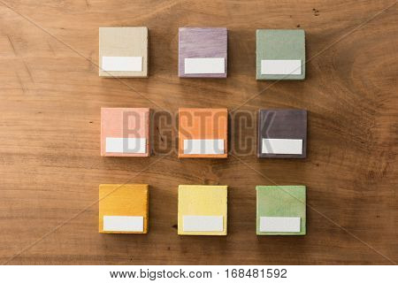 Index, menu or cover abstract back ground, with blank white space for custom text, consisting of nine hand painted colored wooden cubes on grungy wooden background with vintage taste.  Earth tone.