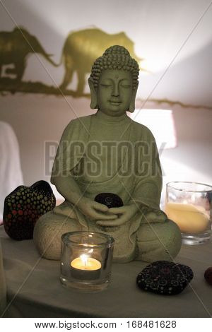 Buddha, Dhyana Mudra symbolizes the spiritual development of the enlightened mind Concentration and meditation, in the foreground Candlelight and happiness stones,   in the background an AirBrush walltatoo with elephant, lamp on the table.