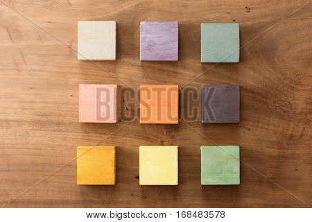 Index, menu or cover abstract back ground, consisting of nine hand painted colored wooden cubes on grungy wooden background with vintage taste.  warm neutral colors. orange, gray, green, beige, pink.