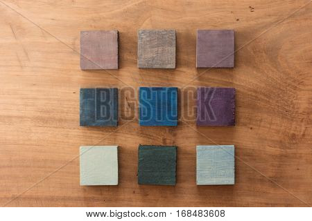 Index, menu or cover abstract back ground, consisting of nine hand painted colored wooden cubes on grungy wooden background with vintage taste.  white, brown, orange, beige, gray.