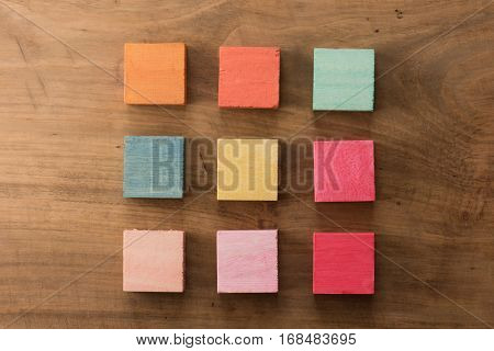 Index, menu or cover abstract back ground, consisting of nine hand painted colored wooden cubes on grungy wooden background with vintage taste.  orange, yellow, blue, pink, magenta.