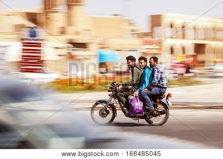 Iran Persia Yazd - September 2016: three guys going at high speed on a motorcycle on the background motion blur. Taking pictures with the wiring.