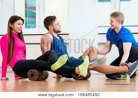 Man and woman with physiotherapist at gym doing floor gymnastics with roll