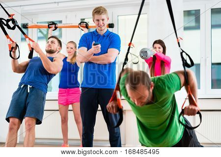 Group of men and women in gym doing workout at rings supervised by physio