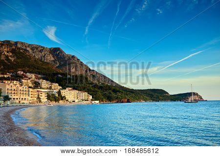 Sveti Stefan sand beach and town view near Budva, Montenegro. Balkans, Adriatic sea, Europe. Sunset time