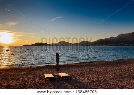 Sveti Stefan sand beach with pair of sunchairs near Budva, Montenegro. Balkans, Adriatic sea, Europe. Sunset time