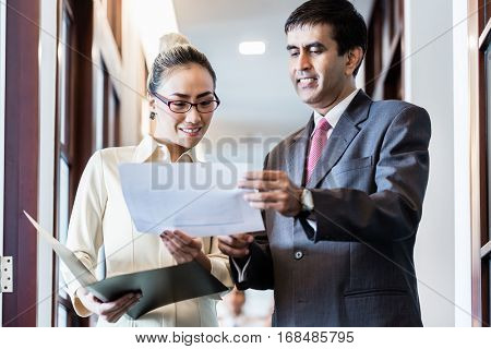 Indian business executive man and Indonesian secretary standing in office hallway discussing papers