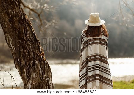 Back Of  Woman Hipster Wearing Hat And Poncho  At Tree Near River, American Outfit, Boho Concept