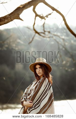 Beautiful Woman Portrait Wearing Hat And Poncho At Tree Near River, American Outfit, Boho Concept
