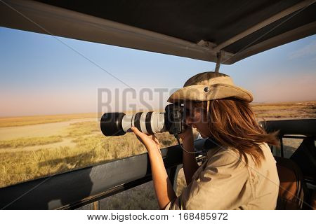Woman tourist taking photo of savannah with professional camera aboard safari jeep in Africa