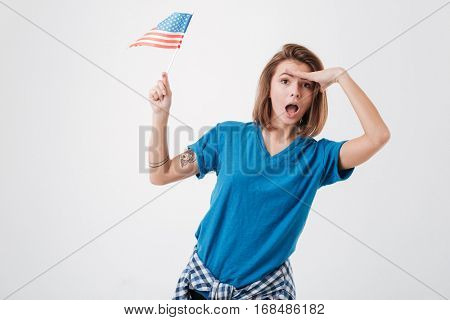 Portrait of an excited young girl with hand on her forehead looking far away and holding american flag isolated on a white background