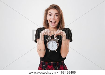 Portrait of a scared young woman holding alarm clock and shouting over white background