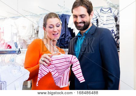 Couple expecting baby buying children wear, woman holding girl clothes in hand