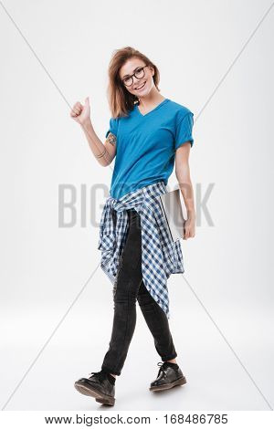 Full length portrait of a cheerful smiling girl in eyeglasses standing and showing thumbs up gesture isolated on a white background