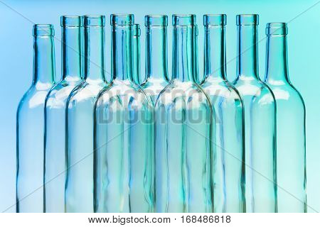 Picture of several clear glass wine bottles on blue background