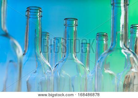 Close-up picture of glass bottlenecks on blue background
