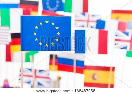 Small paper flag of European Union against flags of EU member-states