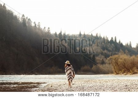 Beautiful Woman Hipster Walking On River Beach In Mountains,wearing Hat And Poncho, Boho Travel Conc