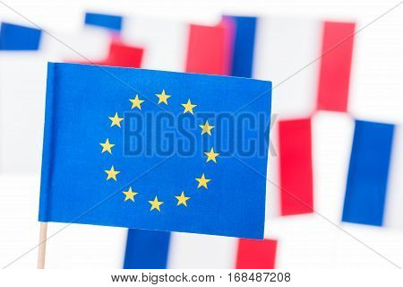Close-up picture of small paper original European Union flag with pole against French flags