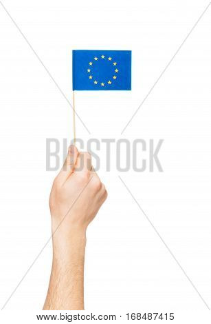 Man's hand holding and raising European Union flag, isolated on white background