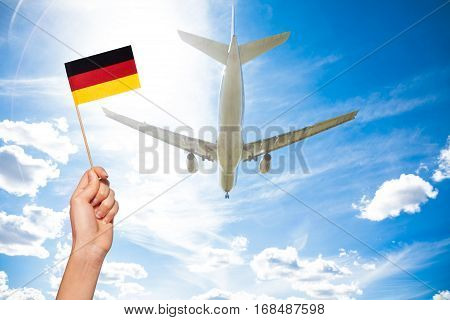 Woman's hand holding German flag with flagpole against the airplane flying through the cloudy sky