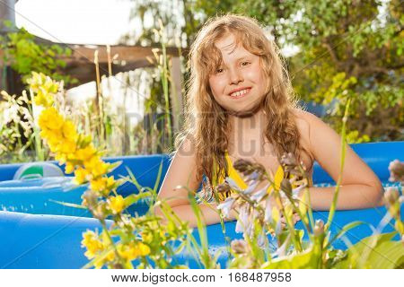 Portrait of beautiful blond ten years old girl posing in the swimming pool outside