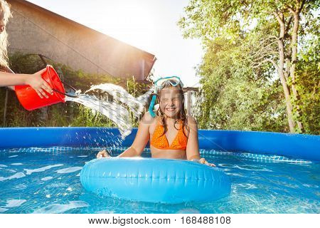 Girl pouring water from a red bucket over her friend in snorkeling mask and tube, swimming with rubber ring in the pool