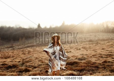 Beautiful Boho Woman Hipster, Smiling And Standing At Sunset In Mountains, Wearing Hat And Poncho, S