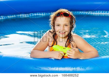 Portrait of happy girl in sunglasses playing with water gun in the blue inflatable pool