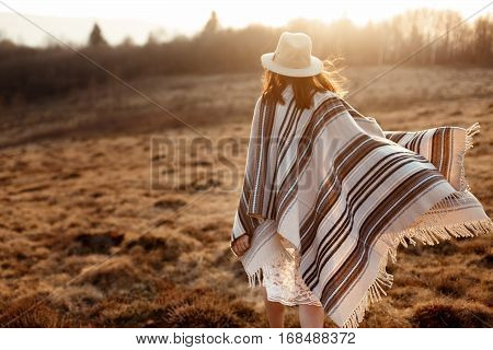 Happy Boho Woman, Walking Towards Sun, Wearing Hat And Poncho At Sunset In Mountains, Space For Text