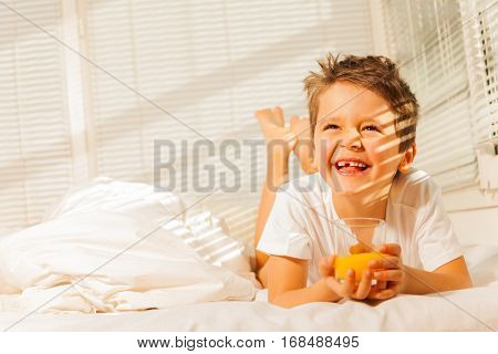 Portrait of smiling boy laying in his bed with glass of fresh orange juice
