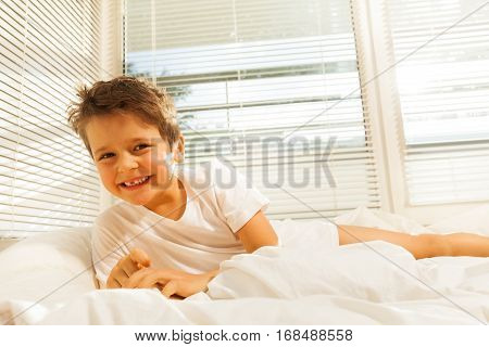 Portrait of cute kid boy smiling while lying on his bed in the morning
