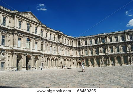 Paris, France - July 3, 2014. Cour Carree courtyard in Paris, Louvre building and people