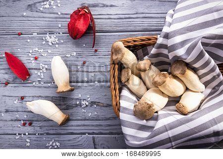 King oyster mushroom Pleurotus eryngii on the gray wooden background, Rustic style